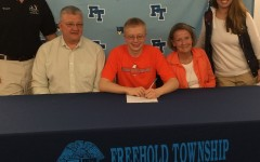 Robert signing his letter of intent; he is surrounded by his parents and his coaches