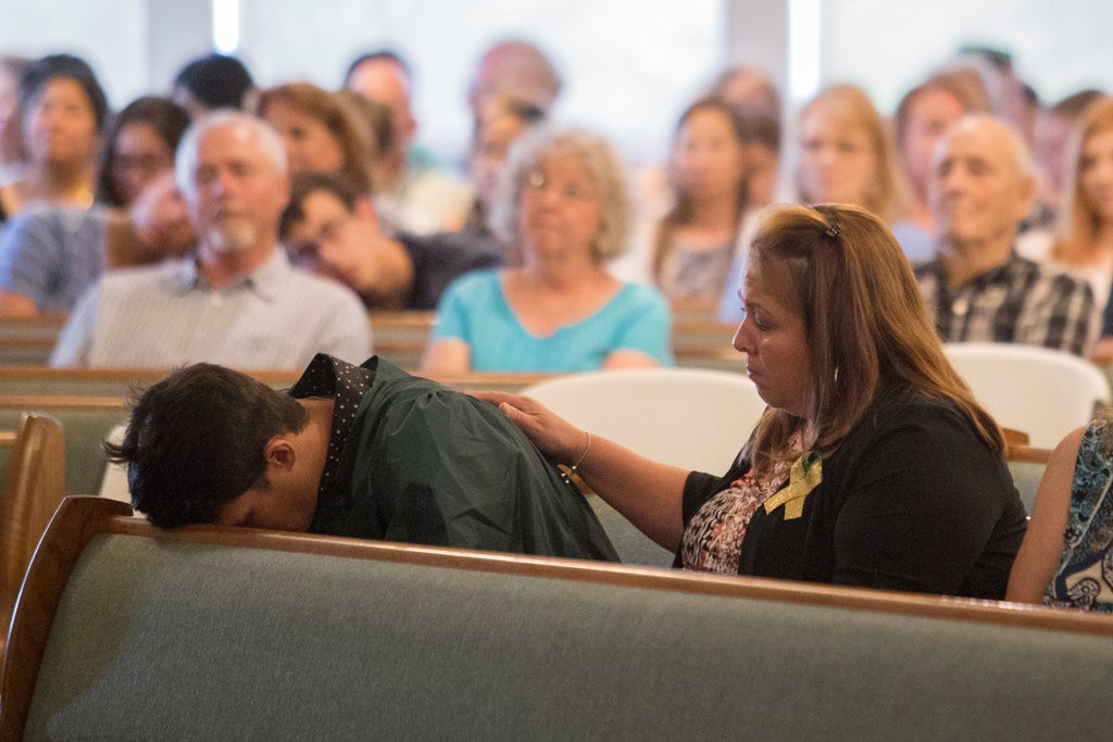 Santa Fe High School seniors sitting with family at a church service in Santa Fe, Tex., following the school shooting. Image courtesy of the New York Times.